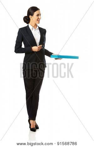 Full length businesswoman giving a binder.