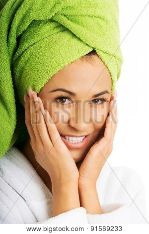 Portrait of a woman in bathrobe touching face.