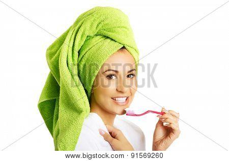 Portrait of a woman in bathrobe brushing teeth.