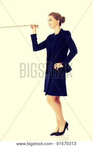 Young beautiful businesswoman holding rope