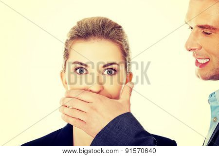 Young man covering woman's mouth