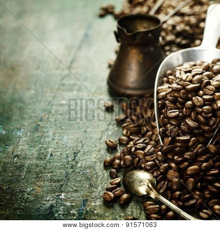 Coffee beans and metal scoop on wooden background