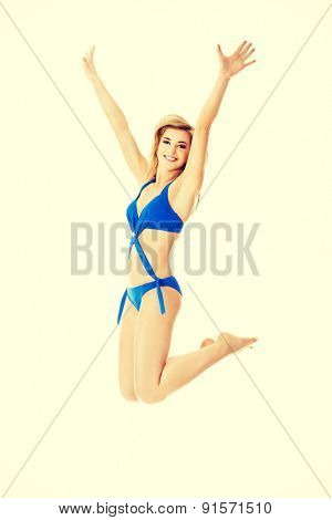 Young blonde woman jumping with her hands up