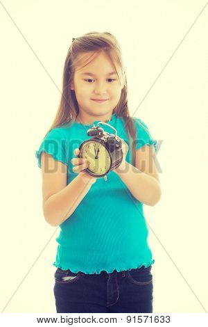 Cute little girl winds the clock