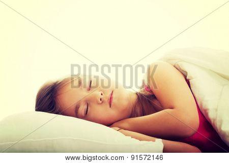 Beautiful brunette girl sleeping in bed