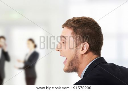 Frustrated businessman screaming at someone.