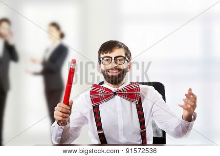 Funny old fashioned man sitting by a desk with big pencil.