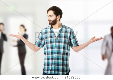 Young caucasian man presenting something in both hands.