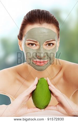 Beautiful spa woman with clay facial mask holding avocado.