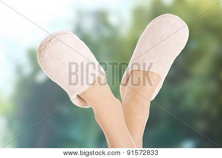 Beautiful female legs in white slippers.