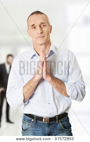 Faithful mature businessman praying before interview.
