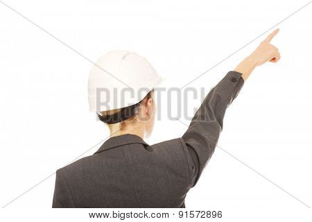Caucasian businesswoman in hard hat pointing up.