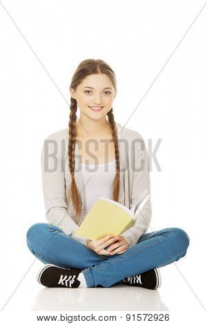 Studying teen woman sitting with her notebook.