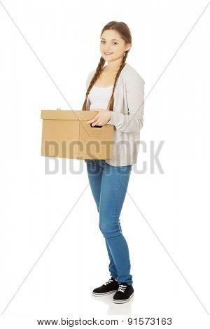 Happy teenage woman holding carton box.