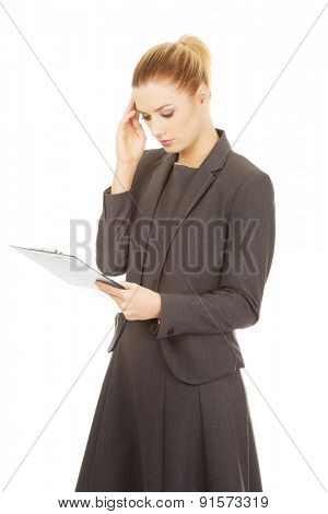 Thoughtful focused businesswoman reading her notes.