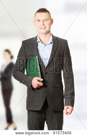 Smiling handsome businessman holding note book.