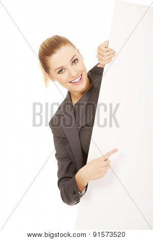 Happy businesswoman pointing on empty banner.