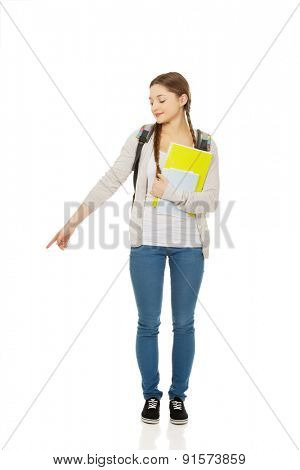Teenager girl with school backpack pointing down.