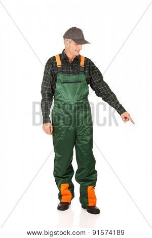 Experienced smiling gardener in uniform pointing down