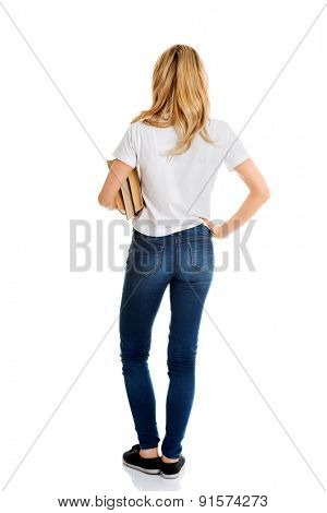 Blond woman standing holding a book, rear view isolated on white