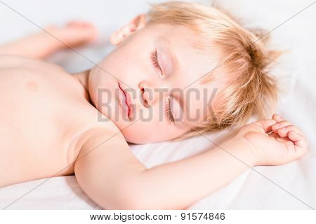 Close-up Portrait Of Handsome Toddler Boy With Blond Hair Sleeping On White Bad