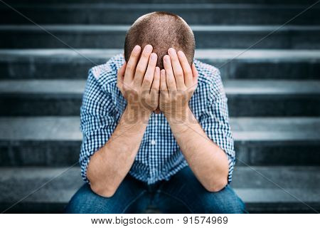 Outdoor Portrait Of Sad Young Man Covering His Face With Hands. Selective Focus On Hands