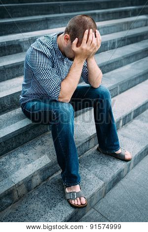 Sad Young Man Covering His Face With Hands Sitting On Stairs Of Big Building