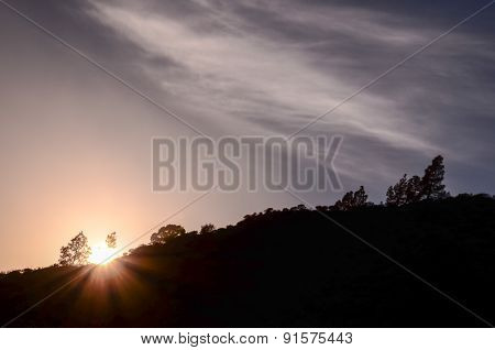 Sun over a Mountain Silhouette