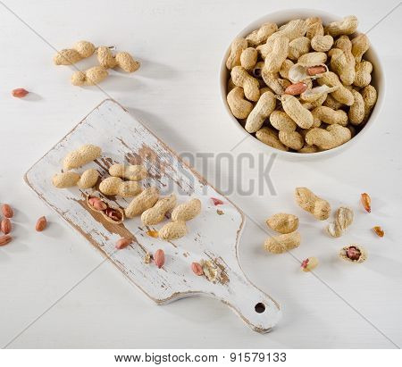 Peanuts In Shells On   White Wooden Background.