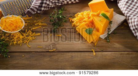 Cheddar Cheese On A Rustic Wooden Background.