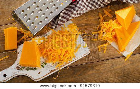Cheddar Cheese On White Cutting Board.