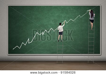 Businesswomen Drawing Financial Chart