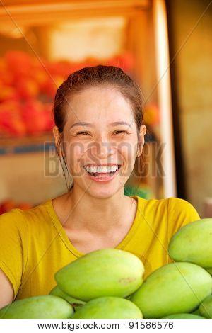 Pretty laughing girl fruit market seller