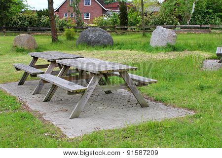 Wooden Tables And Benches On The Meadow