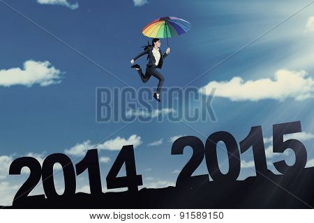 Worker Jumps With Umbrella Above Number 2014 To 2015