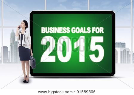 Worker With Billboard Of Business Goals For 2015