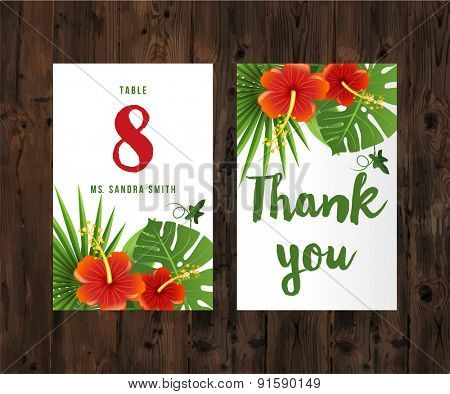 2 cards with tropical leaves and flowers on wooden background