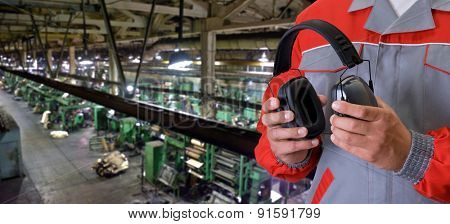 Worker with protective headphone at man hands at industrial factory