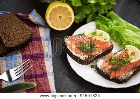 Homemade sandwich with salmon and rye bread , butter lemon, and lettuce for breakfast