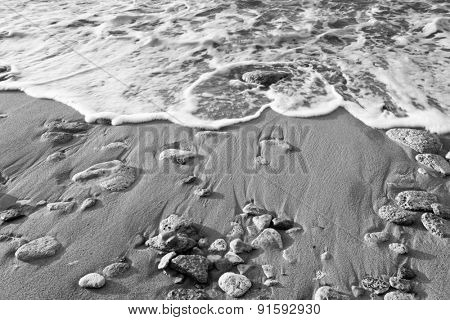 Black & White - Wave of the sea on the beach with sand and stones at the early morning