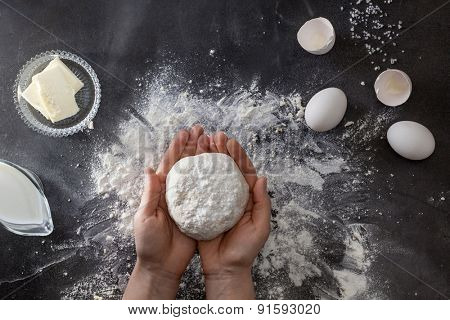 Woman's hands knead dough on table with flour and ingredients. Top view.