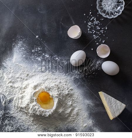 Dough on black table with flour and ingredients. Top view
