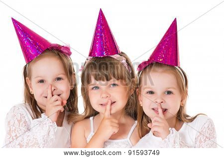 Three cute little girls say silence is a secret