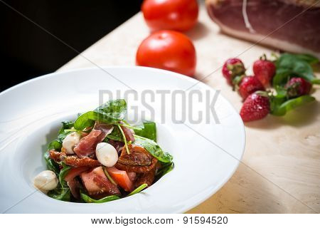 Salad with strawberry, prosciutto, herbs, cottage cheese and blackberry balsamic vinegar.