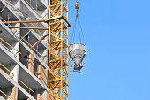 image of mixer  - Crane lifting concrete mixer container against blue sky - JPG
