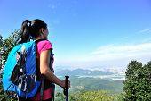 stock photo of wilder  - woman hiker looking into the wilderness on mountain peak - JPG