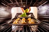 foto of oven  - Baking Gingerbread man in the oven - JPG