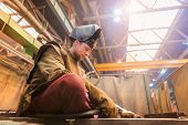 pic of protective eyewear  - Young man with protective mask welding in a factory - JPG