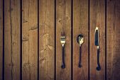 picture of rapier  - Vintage antique style cutlery a fork spoon and knife with twirled design metal stems against a natural wooden board background - JPG