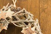 image of pine cone  - closeup of christmas decoration with twigs brown pine cone and wooden stars on wooden background - JPG